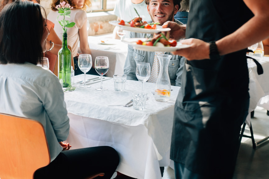 Waiter Serving Delicious Food to Young Couple in Restaurant
