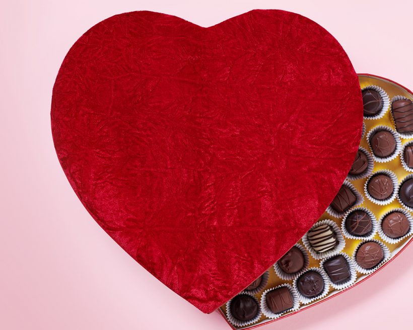 Chocolates in a red, heart-shaped box on a pick background