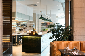 A high-ceilinged restaurant with an open kitchen