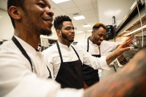 Onwuachi with chefs Richard and Martel in Kith/Kin's kitchen