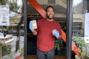 A man holds a quart container filled with margaritas