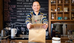 Waiter handing a bag of take out food