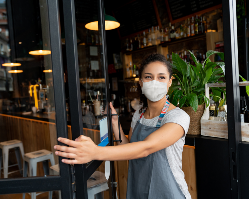 A masked server opens the door of a restaurant