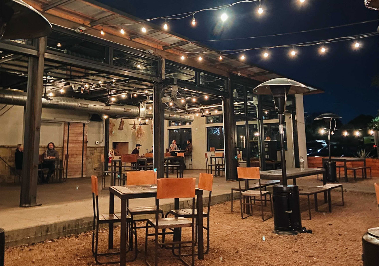 An outdoor patio with heaters and string lights.