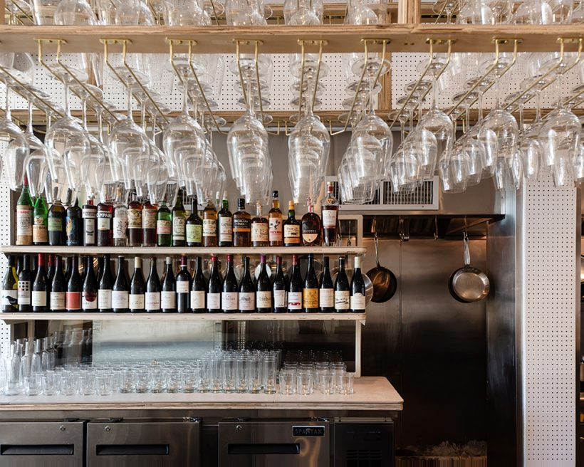 A bar with wine glasses stacked above it