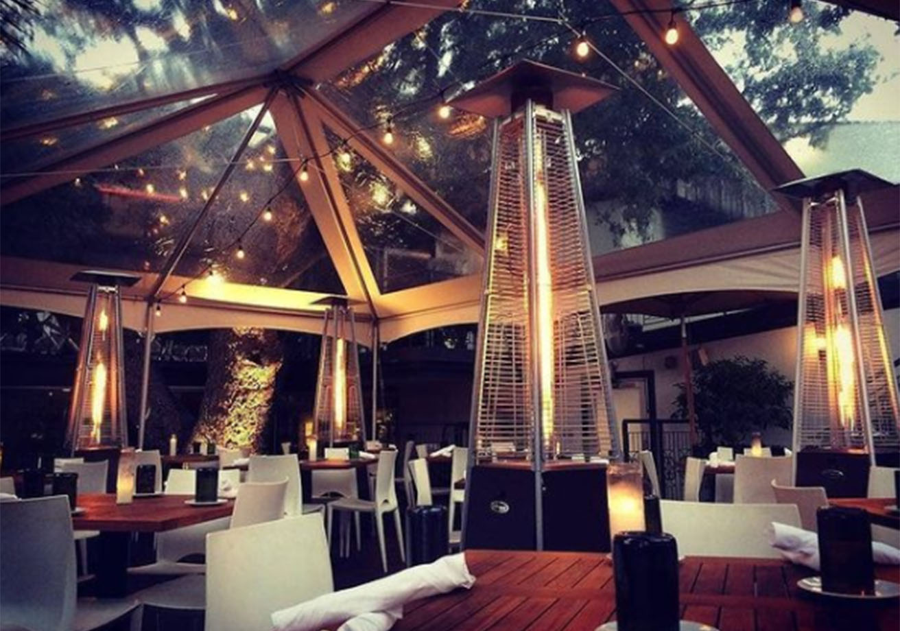 Outdoor dining tables under a tent next to heaters.