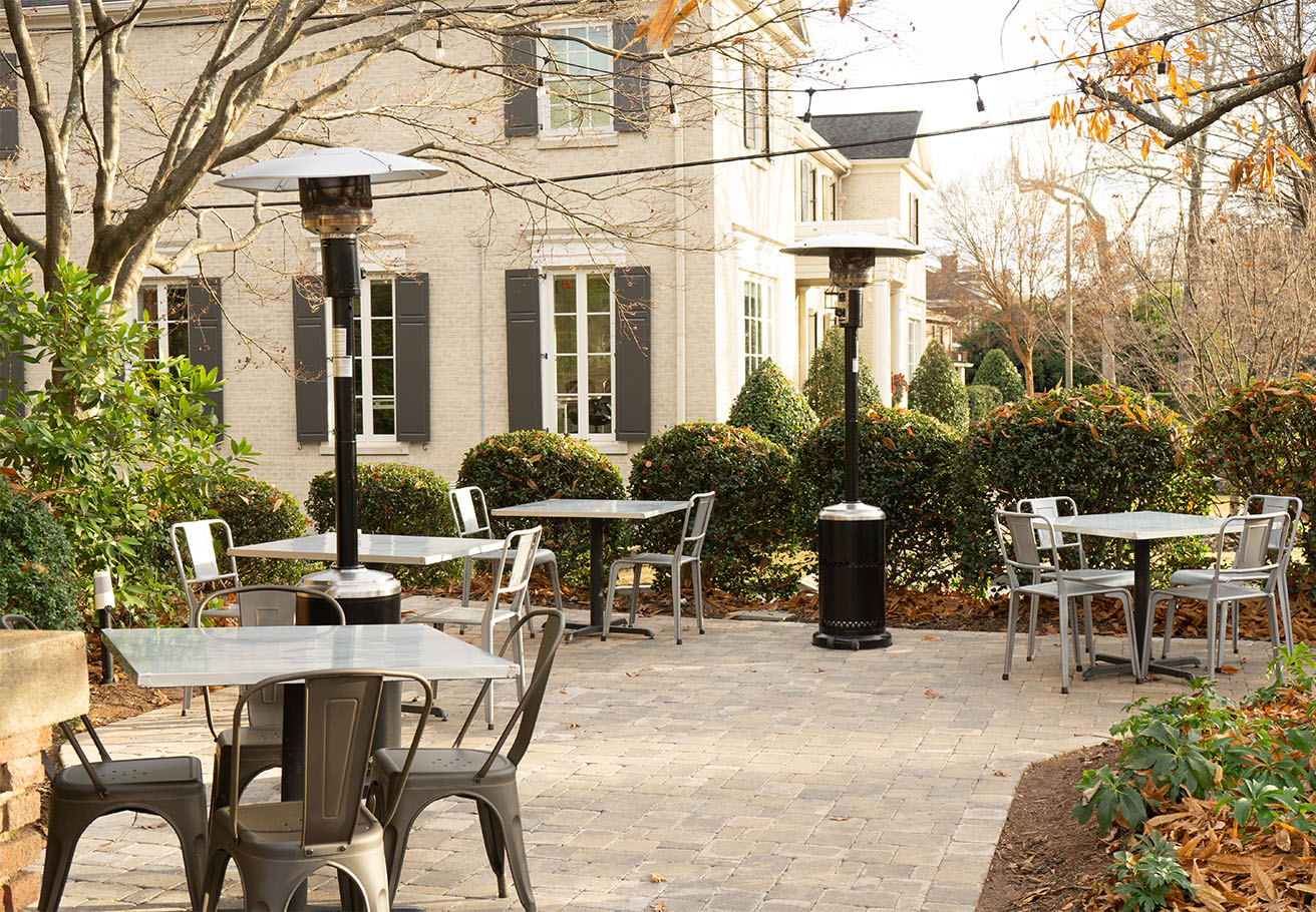 Dining tables under heaters on a patio.
