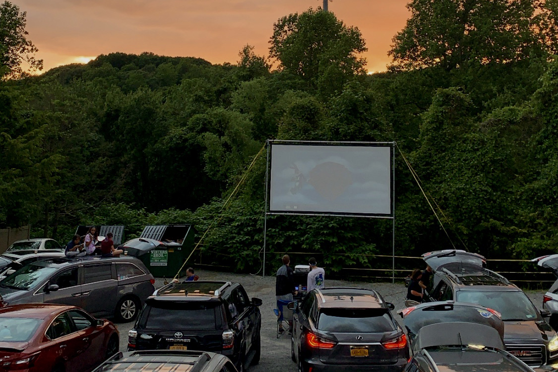 Cars park to watch a movie in a lot