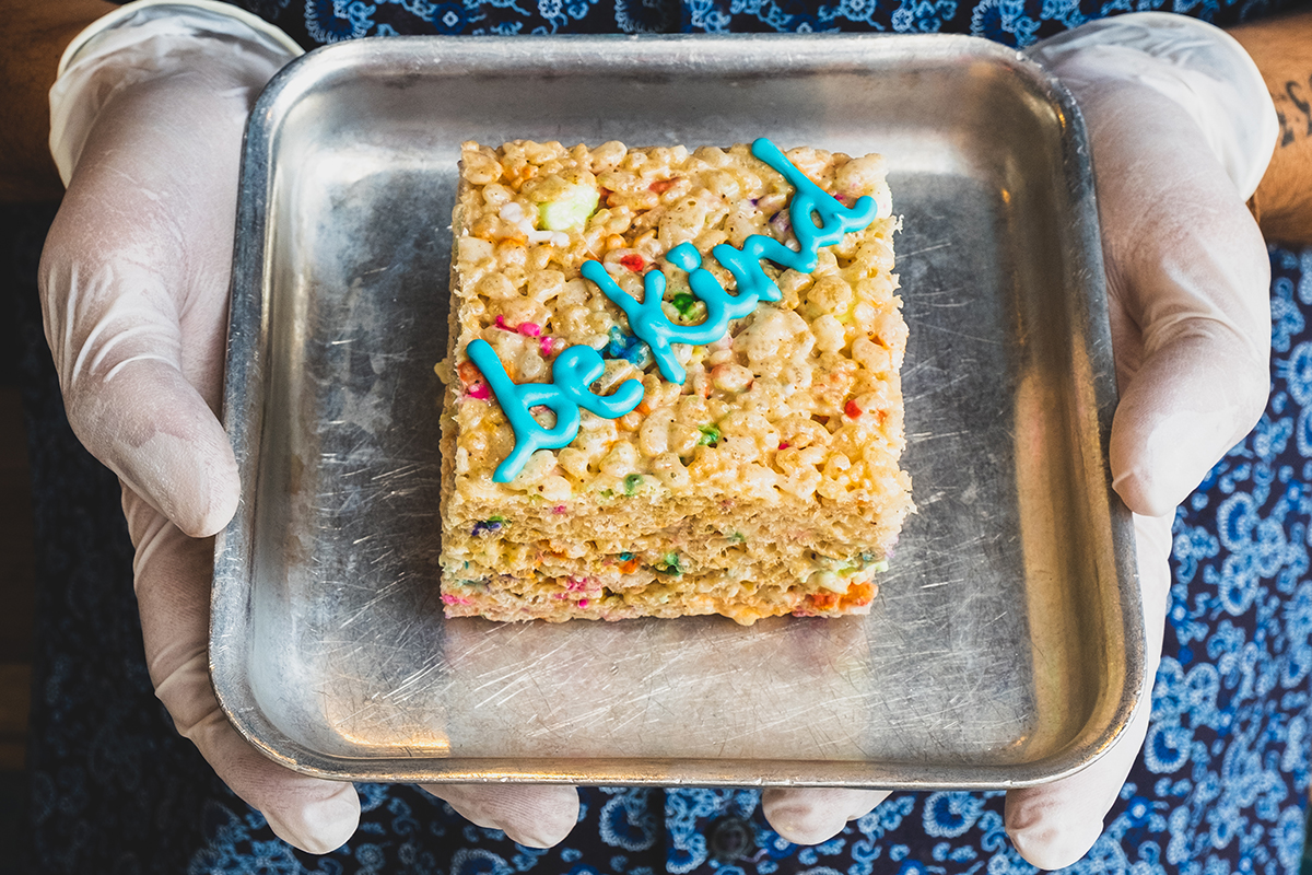 "A crispy rice cereal treat that says ""be kind"" in frosting"