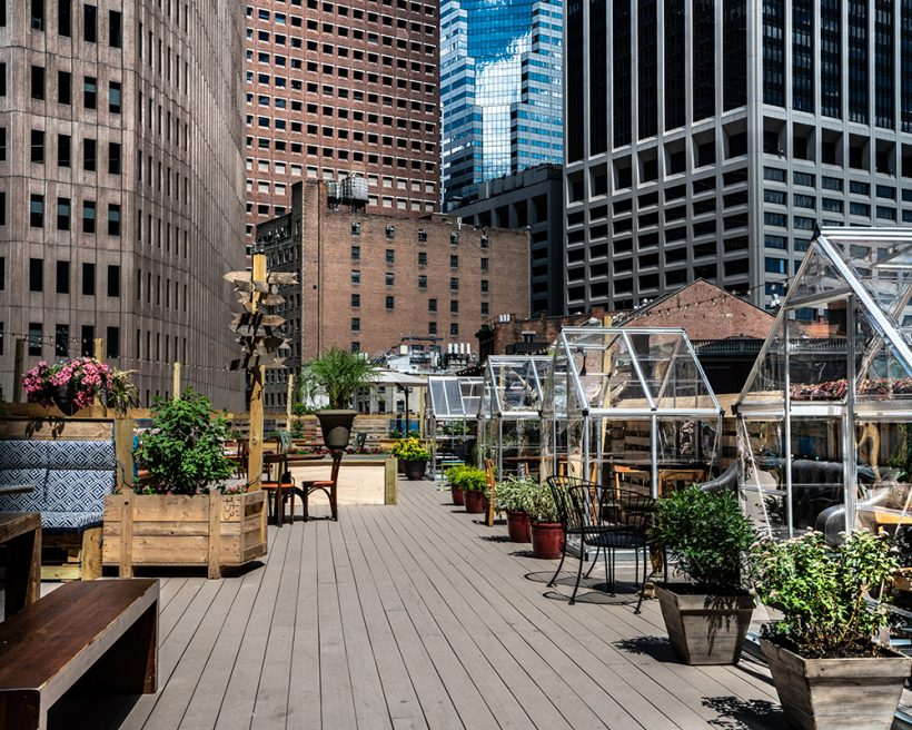 An NYC rooftop with tables in plastic greenhouses