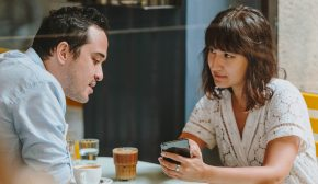 Two people look at a phone at a table