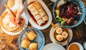 A table laden with Chinese dim sum and human hands picking up with chopsticks