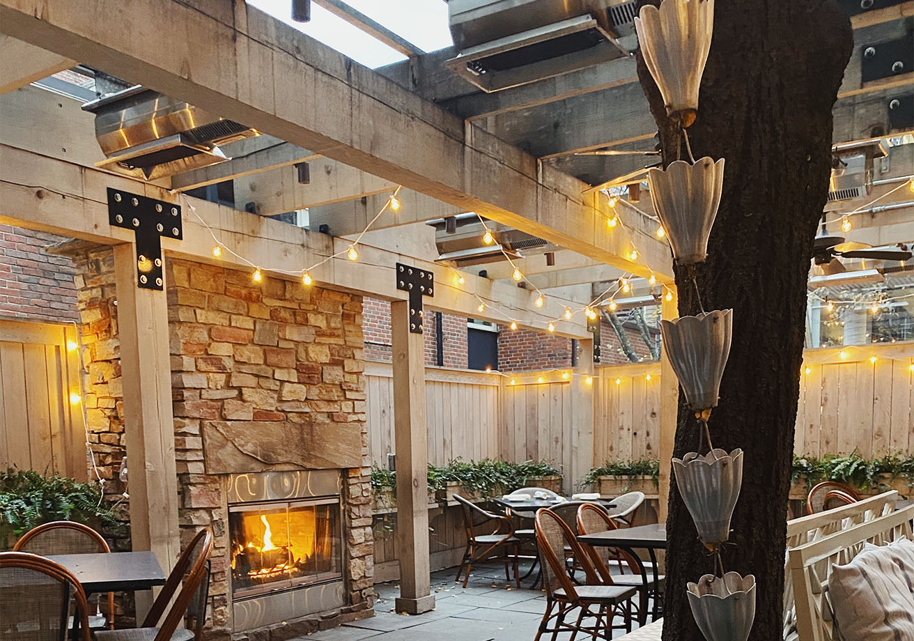 Outdoor tables on a patio with a fireplace.