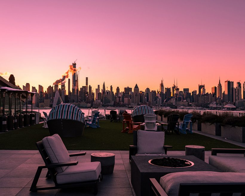 Chairs and tables on a rooftop with the New York City skyline beyond