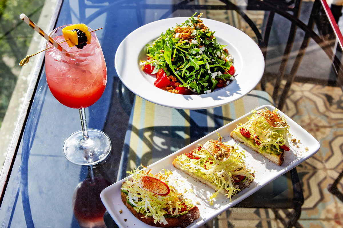 A cocktail and two dishes on a table