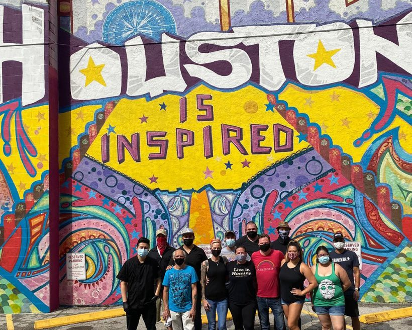 "Houston restaurant workers take a photo in front of a ""Houston is inspired"" mural"
