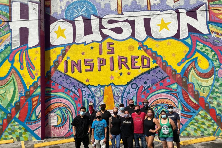"""Houston restaurant workers take a photo in front of a """"Houston is inspired"""" mural"""