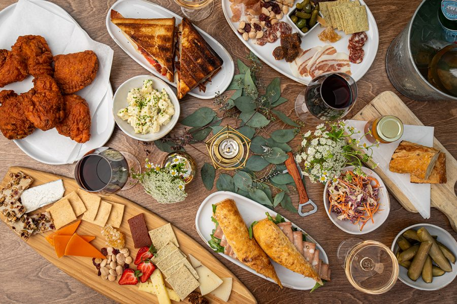 A spread of dishes including fried chicken, charcuterie, and sandwiches