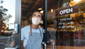 A masked restaurant worker opens the door