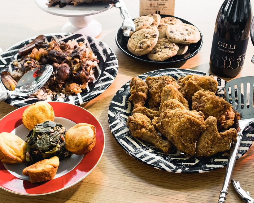 A spread of food including fried chicken, chocolate chip cookies, and red wine