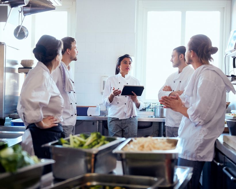 Female chef holding a digital tablet while discussing with team in kitchen