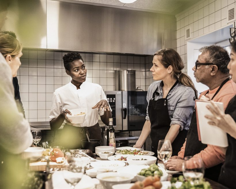 A Black chef demonstrates how to make a dish to her employees