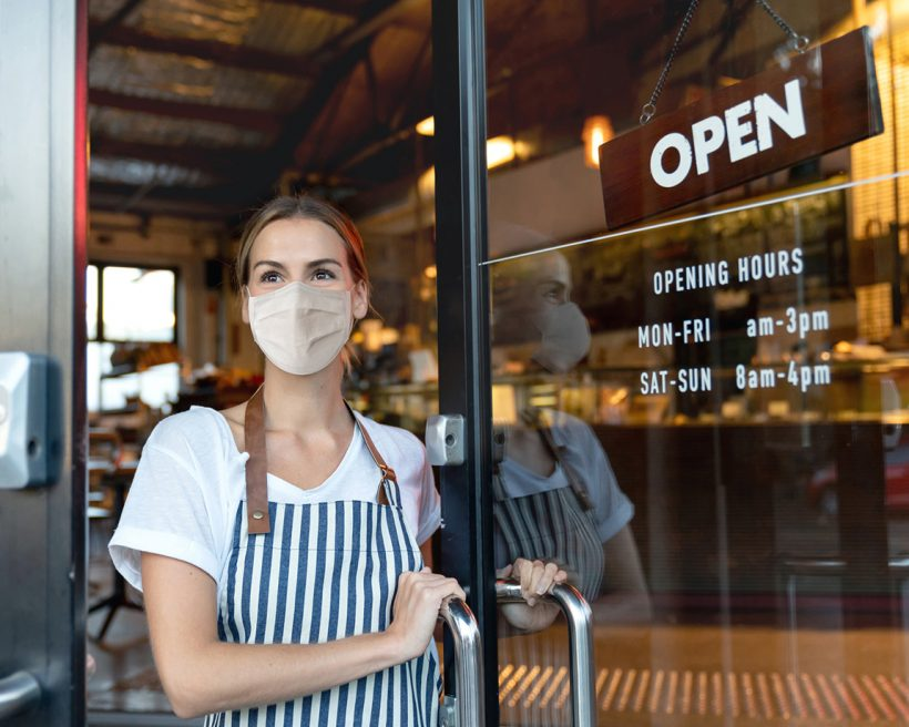 Happy business owner opening the door at a cafe wearing a face mask