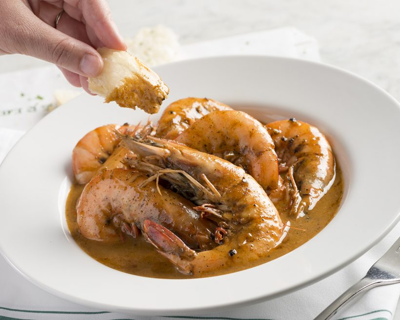 A hand dipping bread into barbecue shrimp