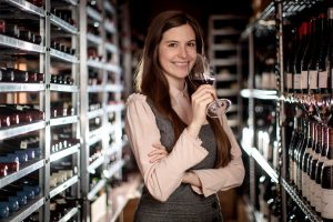 Victoria James posing in a wine cellar with a glass of red wine