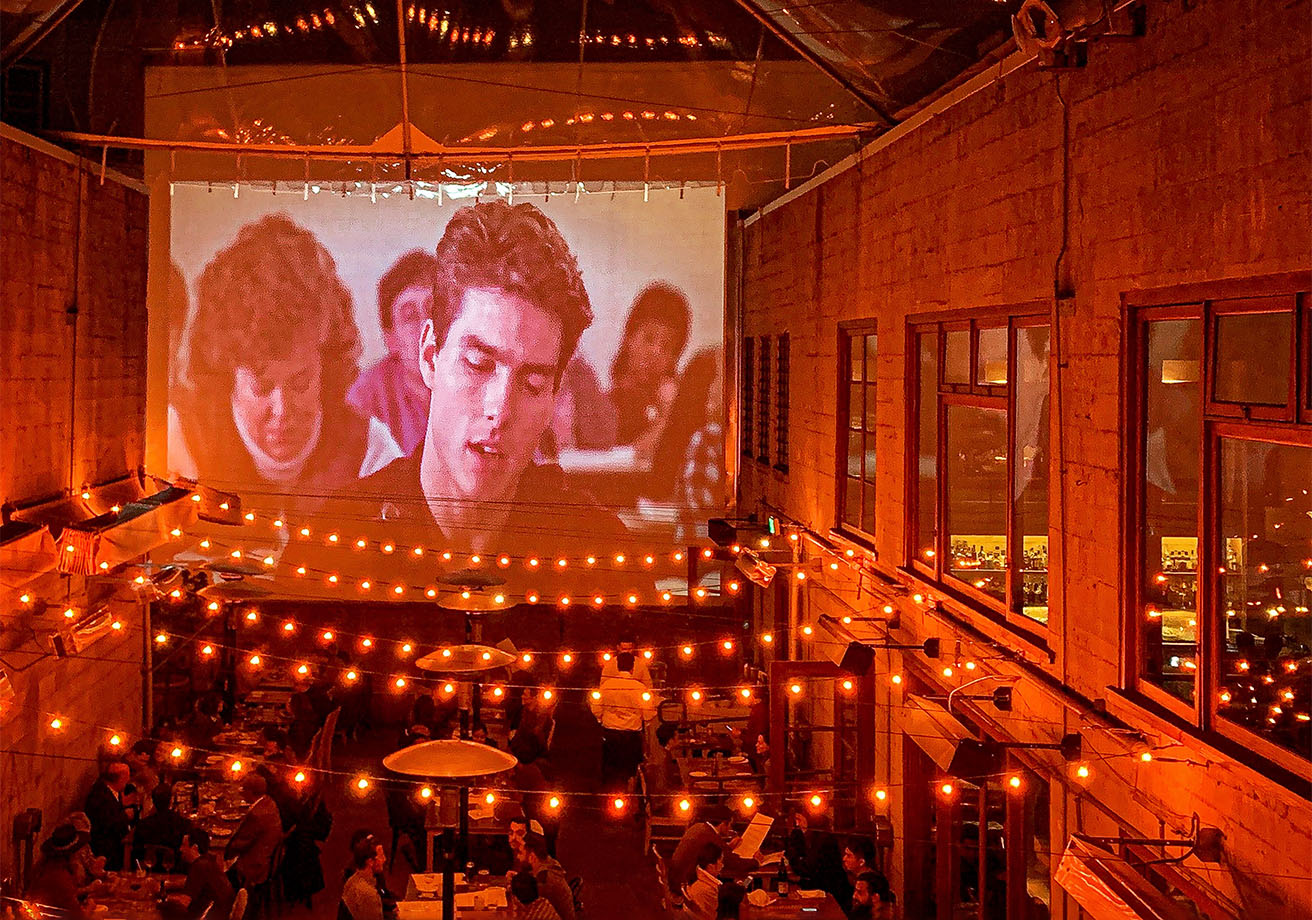 A movie is projected on a wall while people dine on a patio below