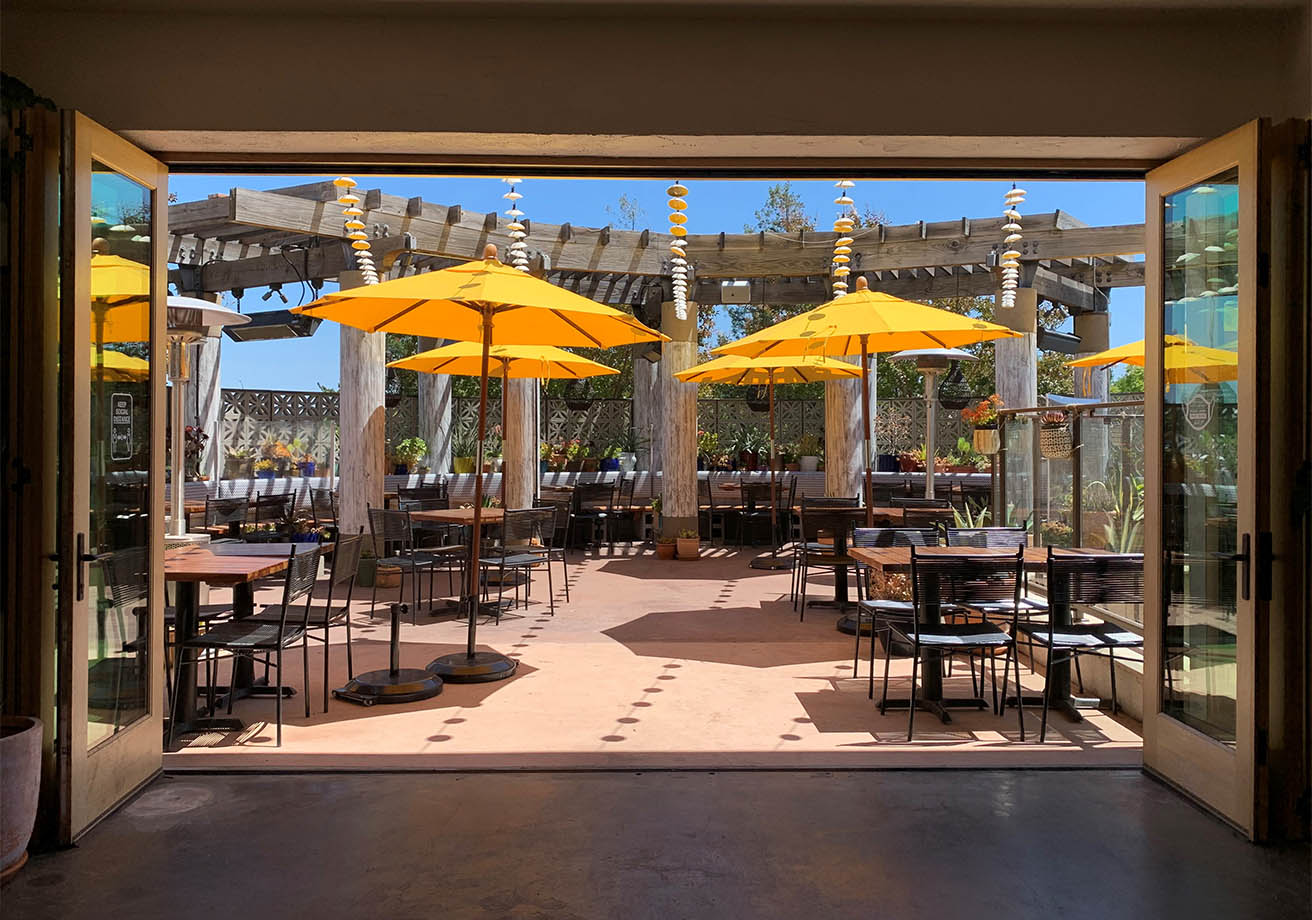 Patio tables sit under umbrellas and heat lamps