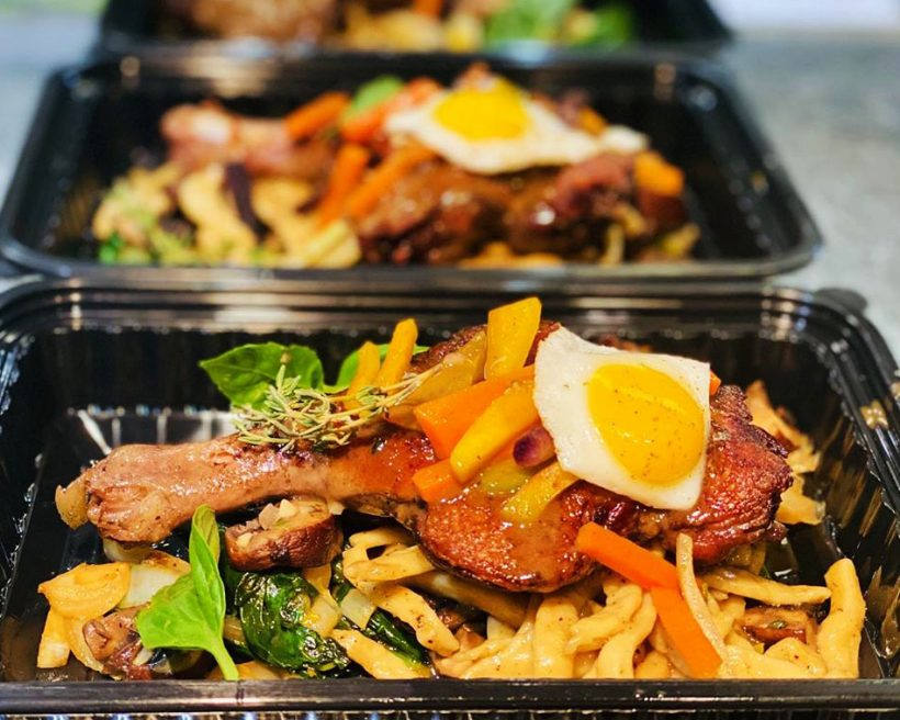 Duck confit in a takeout container with an egg on top
