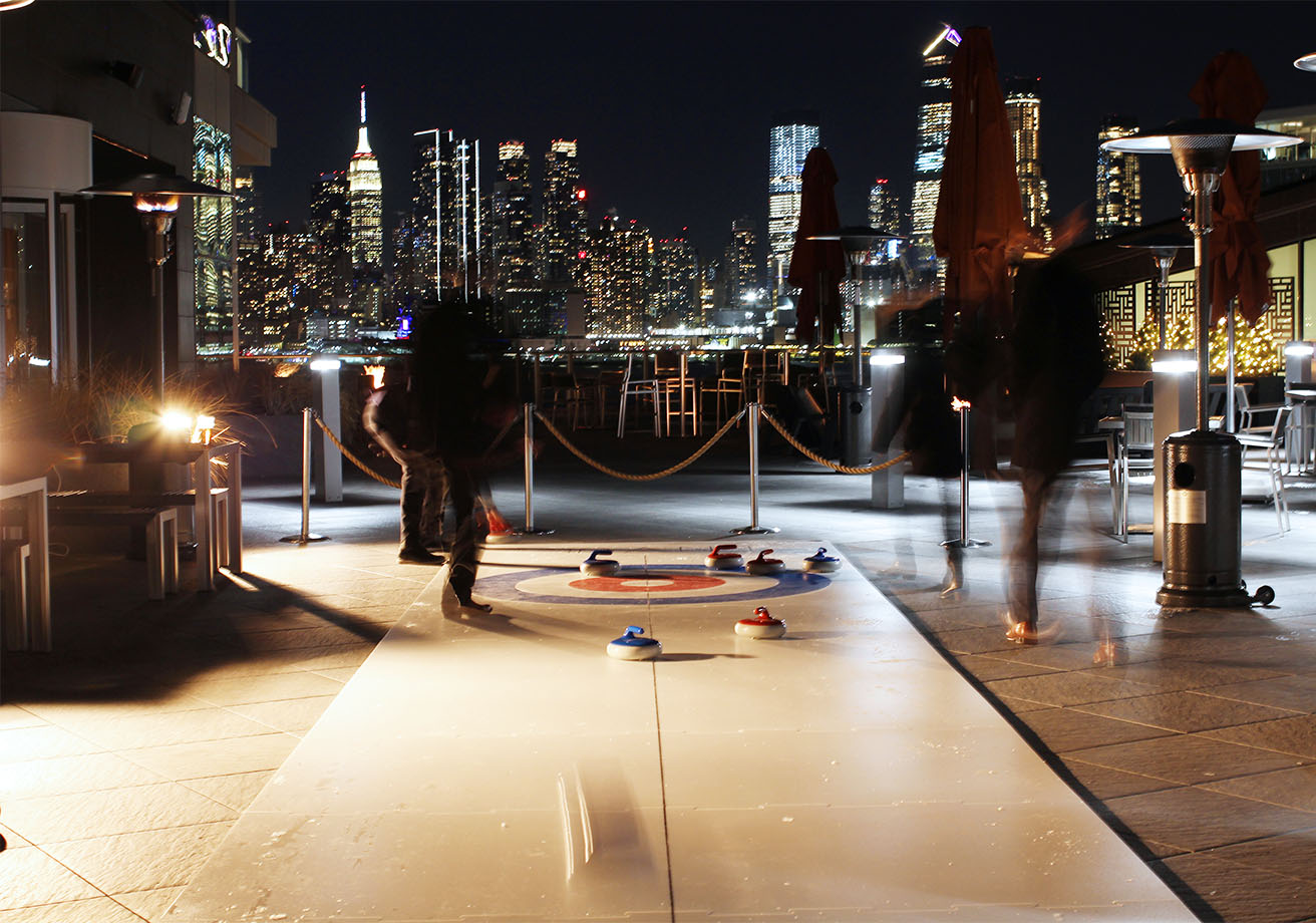People curling on an outdoor rooftop.