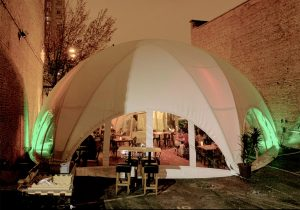 Outdoor dining tables under a white tent.