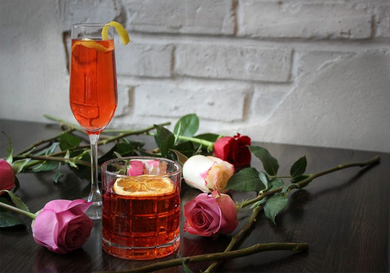 Two cocktails on a table with roses