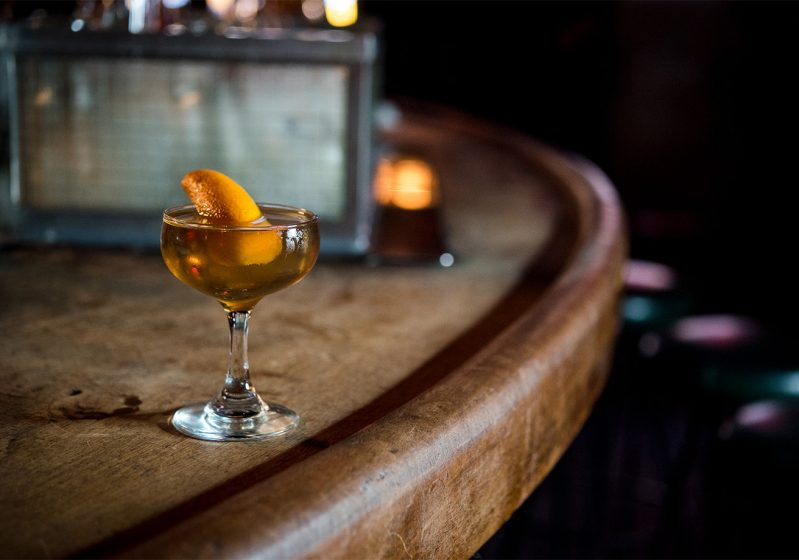 A whisky cocktail sits on a wooden bar.