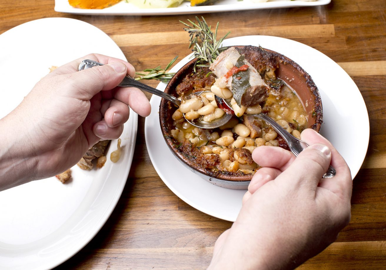 A person spoons beans out of a bowl of cassoulet.