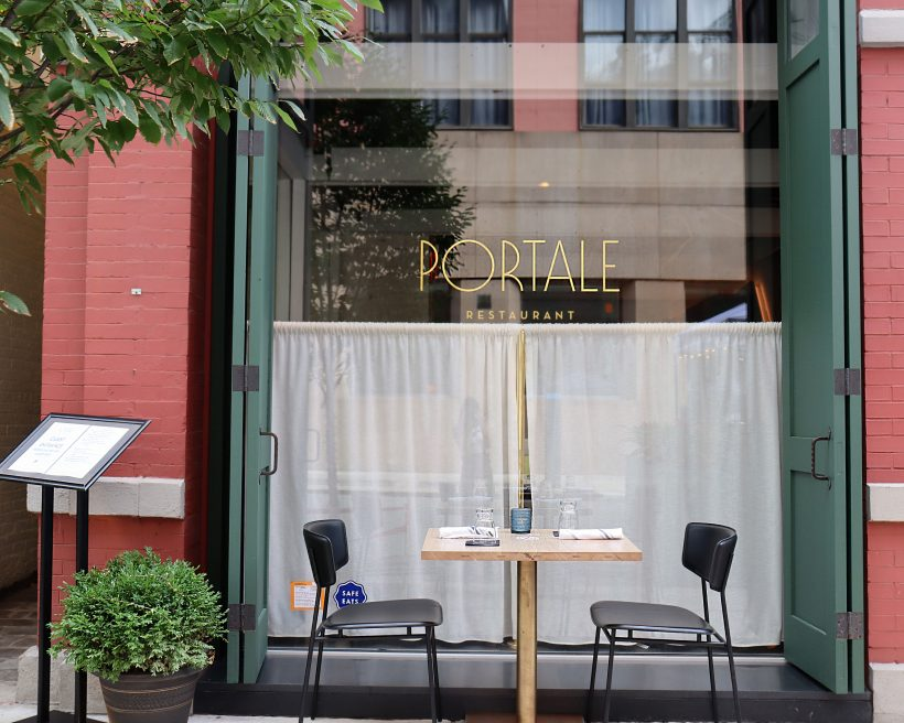 A table for two in front of a restaurant window.