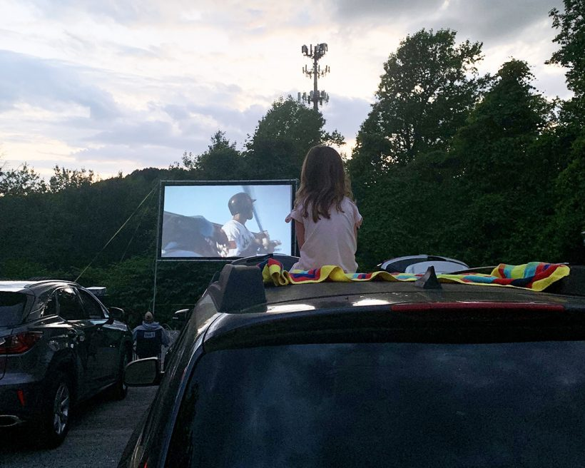 A child sits on top of a car at a drive-in movie