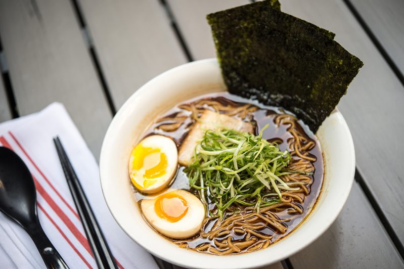 A bowl of ramen sits on a table.
