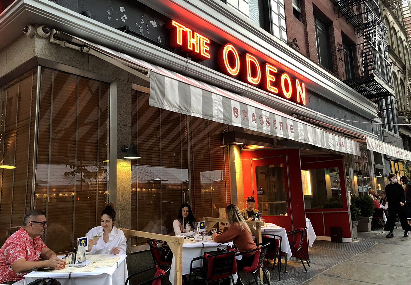 Diners sitting at outdoor tables in front of The Odeon.