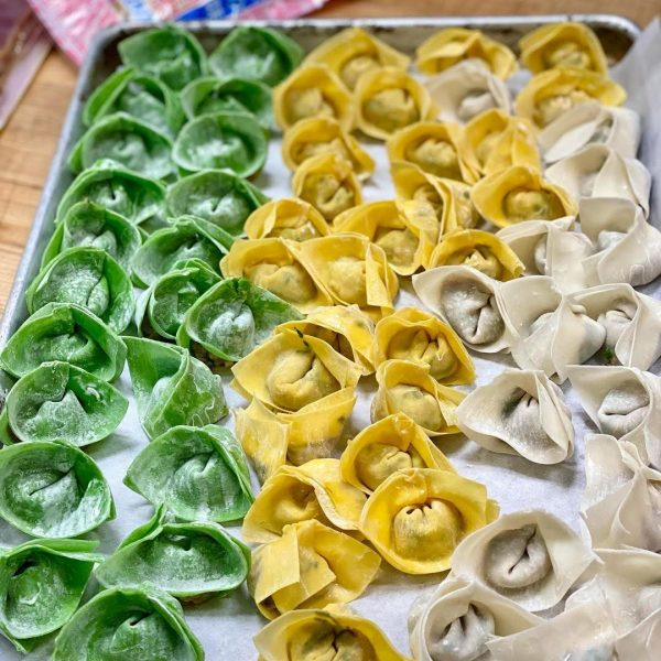 Green, yellow, and white wontons on a sheet tray