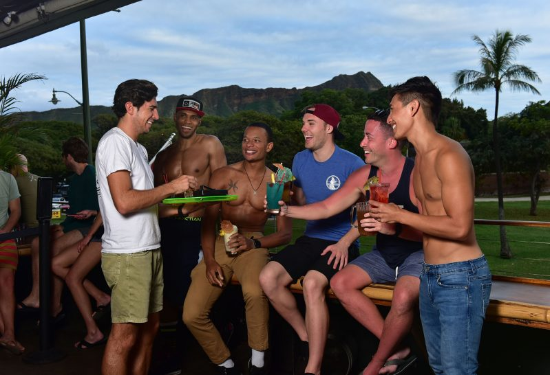 A server hands out drinks to a group of men.