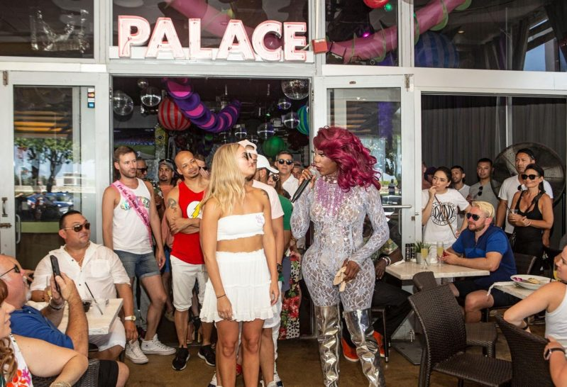 A drag performer talks into a microphone next to a diner.